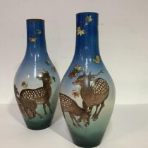 An unusual pair of Satsuma vases, c. 1900/1920, of slender baluster form, boldly painted with Sika