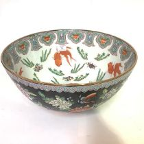 A large Chinese famille noir porcelain punch bowl, the interior painted with carp amidst fronds, the