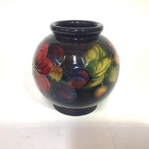 A Moorcroft pottery vase in the Clematis pattern, of globular form, against a blue ground, with