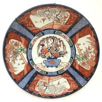 A large Japanese Imari porcelain charger, c. 1900, the well painted with a vase of flowers, the
