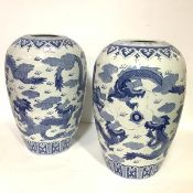 A pair of Chinese blue and white porcelain jars, 20th century, decorated with dragons and flaming