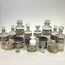 A group of late 19th/early 20th century clear glass pharmacy jars each with red and gilt label