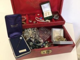 A jewellery box containing a quantity of costume jewellery including rings, brooches, necklaces, a