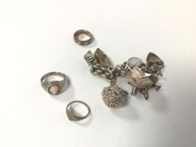 A silver charm bracelet, with most charms marked 'silver' and two silver rings and another (charm
