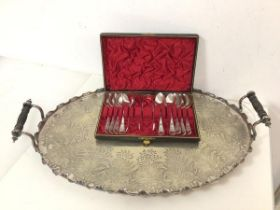 An Epns drinks tray with raised ebonised handles, with oval scalloped edge and foliate engraved base