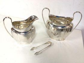 A 1920s Birmingham silver milk jug and a two handled sugar bowl with sugar nips (combined: 383.