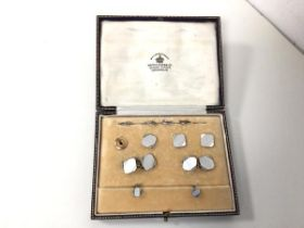 A set of 8ct and 9ct gold engine turned sleevelinks and studs, retailed by Mappin & Webb, in