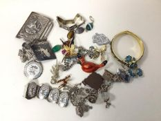 A collection of silver and costume jewellery including charm bracelets, belt buckle, bracelets,