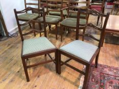A pair of early 20thc side chairs with pierced yoke ladder backs and upholstered drop in seats, on