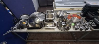 The contents of a table of assorted pots, pans, jugs & other kitchen related items