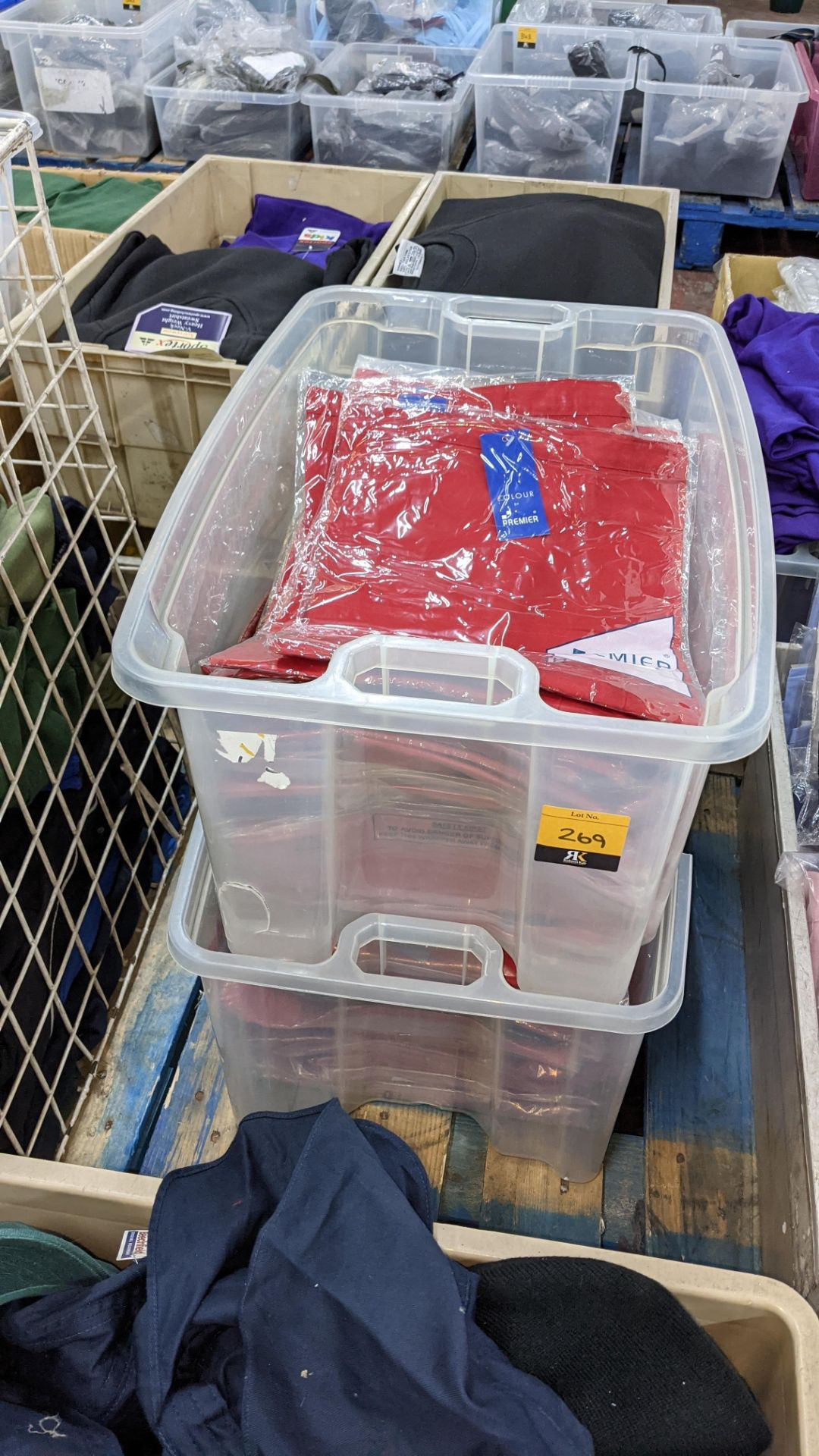Approx 60 off red aprons - the contents of 2 crates. NB crates excluded