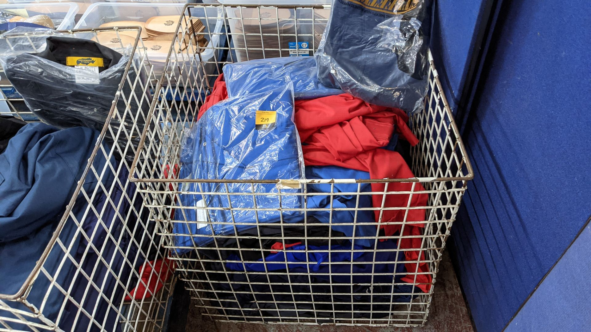 The contents of a cage of assorted work clothing. NB cage excluded