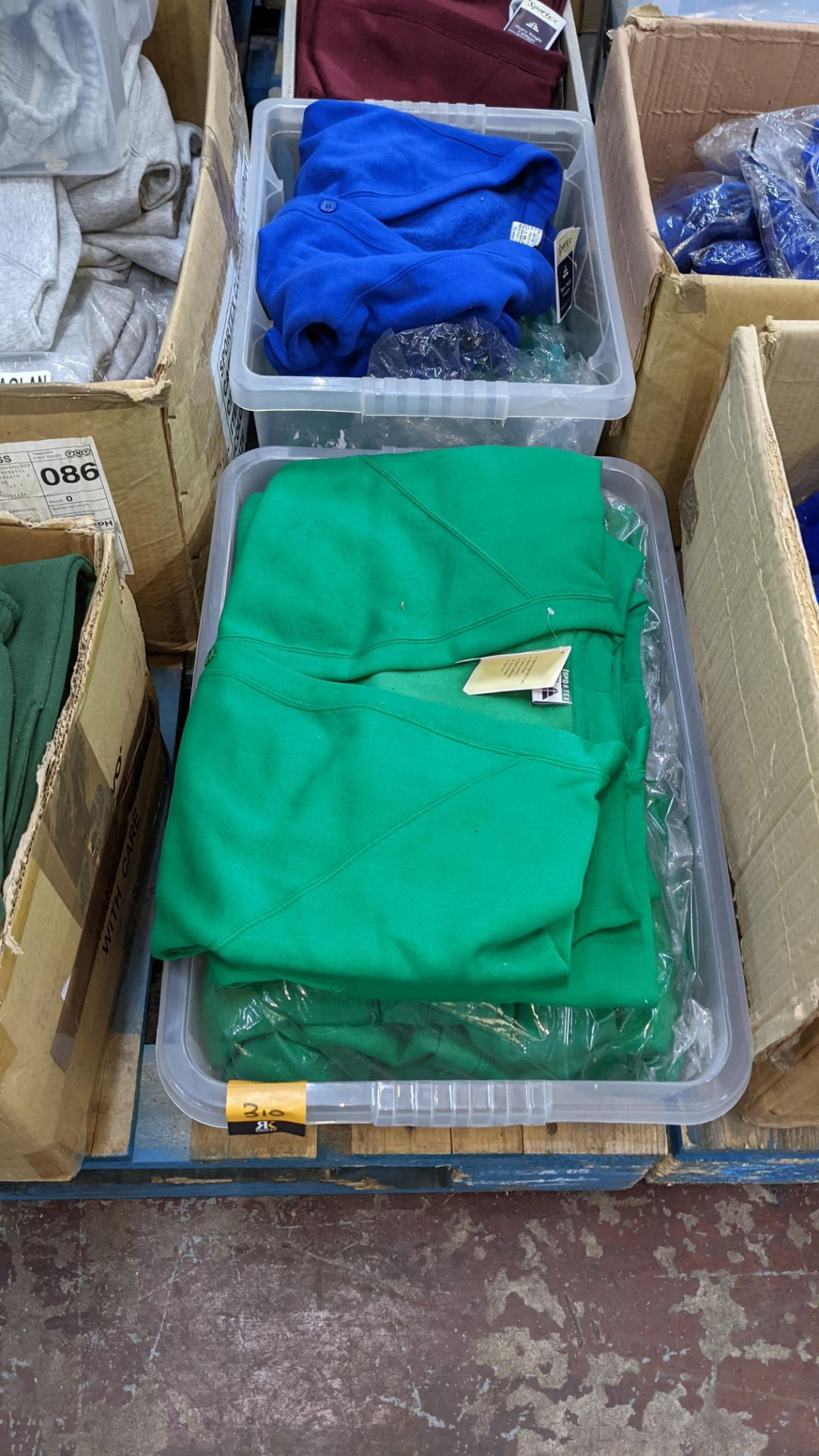 The contents of 2 crates of green & blue button up children's sweat tops & similar. NB crates exclu