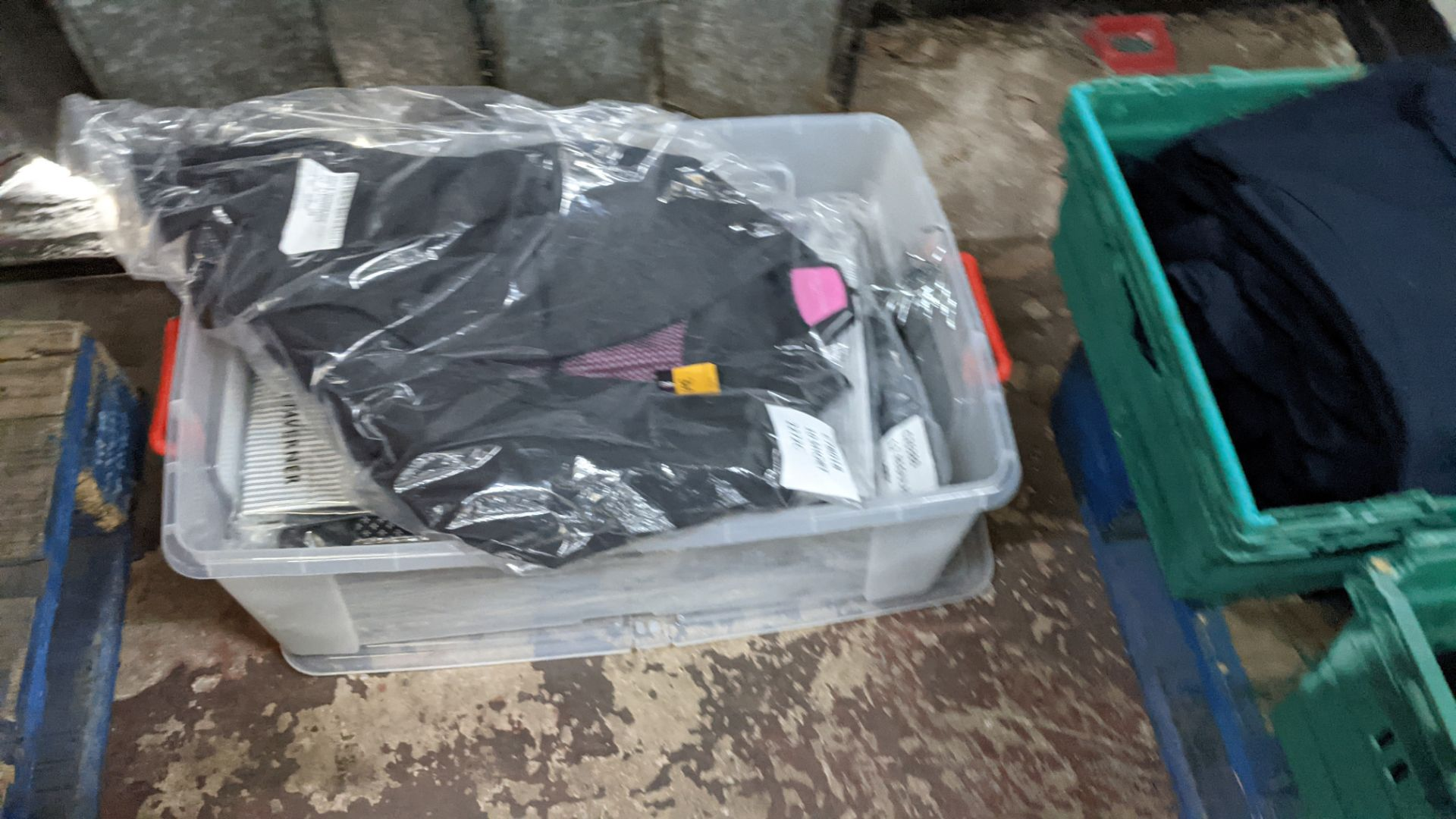 Quantity of assorted garments comprising the contents of a crate. NB crate excluded