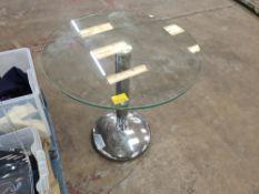 Circular glass table with single pedestal silver base