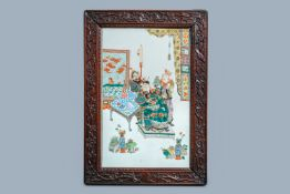 A large Chinese famille verte plaque in a sculpted wooden frame, 19th C.