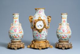 A Chinese gilt bronze-mounted three-piece Canton famille rose clock garniture, 19th C.