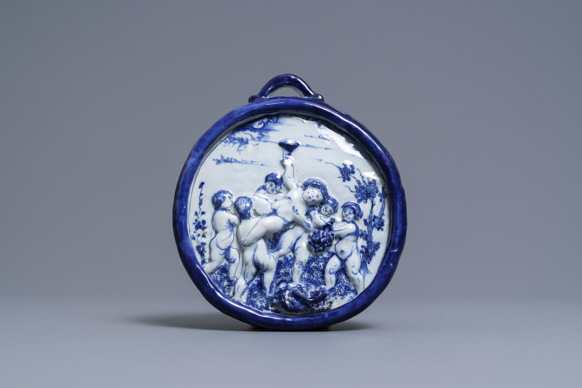 A Dutch Delft blue and white relief-moulded plaque with putti holding grapes, 18th C.