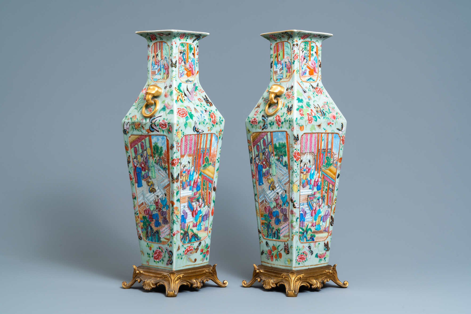 A pair of Chinese square famille rose celadon-ground vases on gilt bronze feet, 19th C.