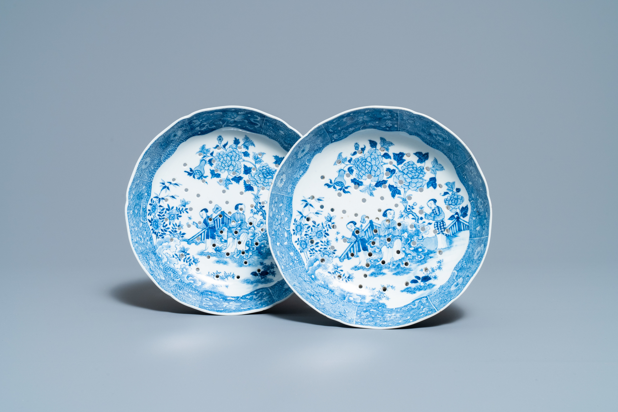A pair of Chinese blue and white strainer dishes with ladies in a garden, Qianlong