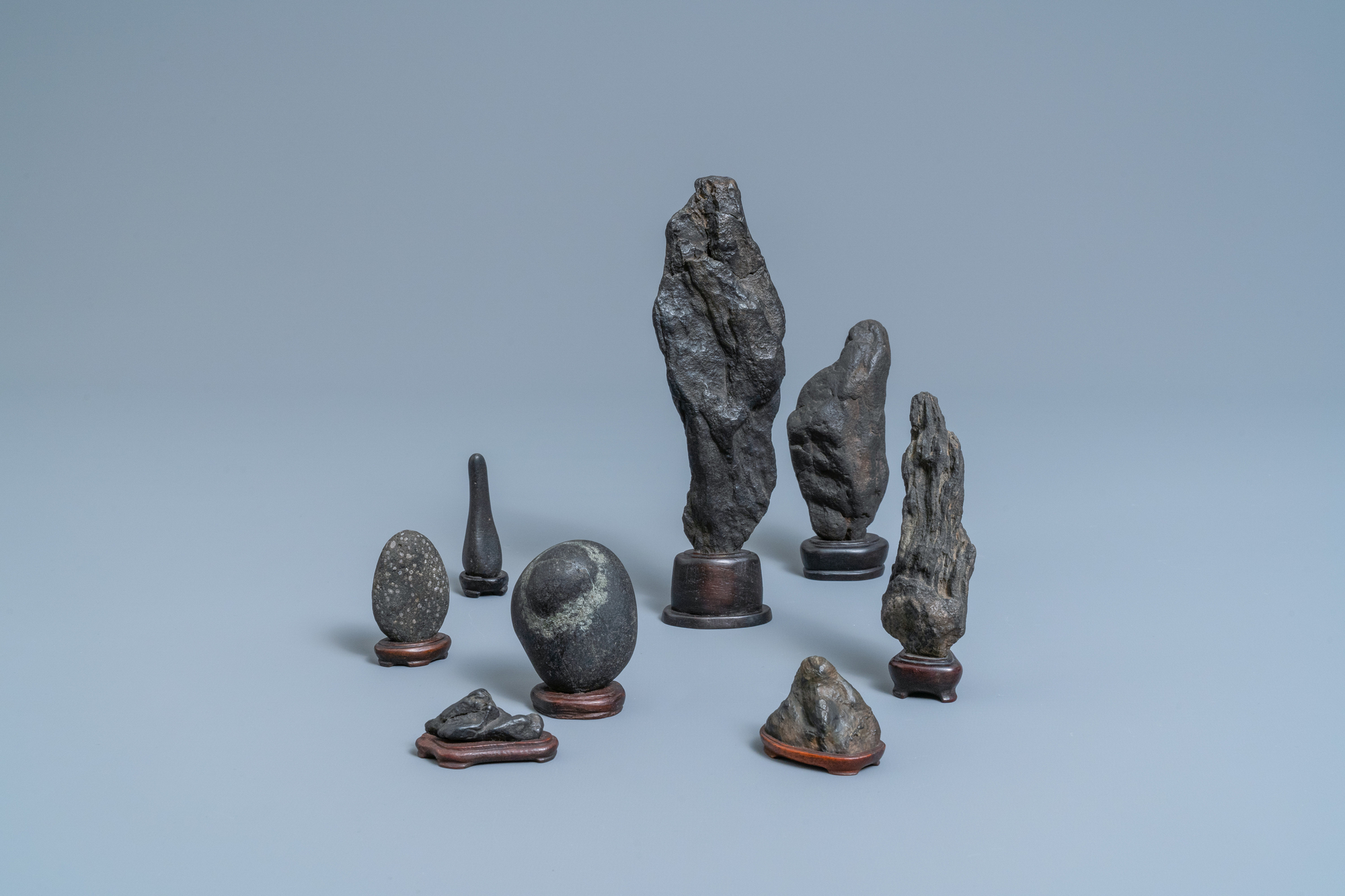 Eight Chinese scholar's rocks on wooden stands, 19/20th C.