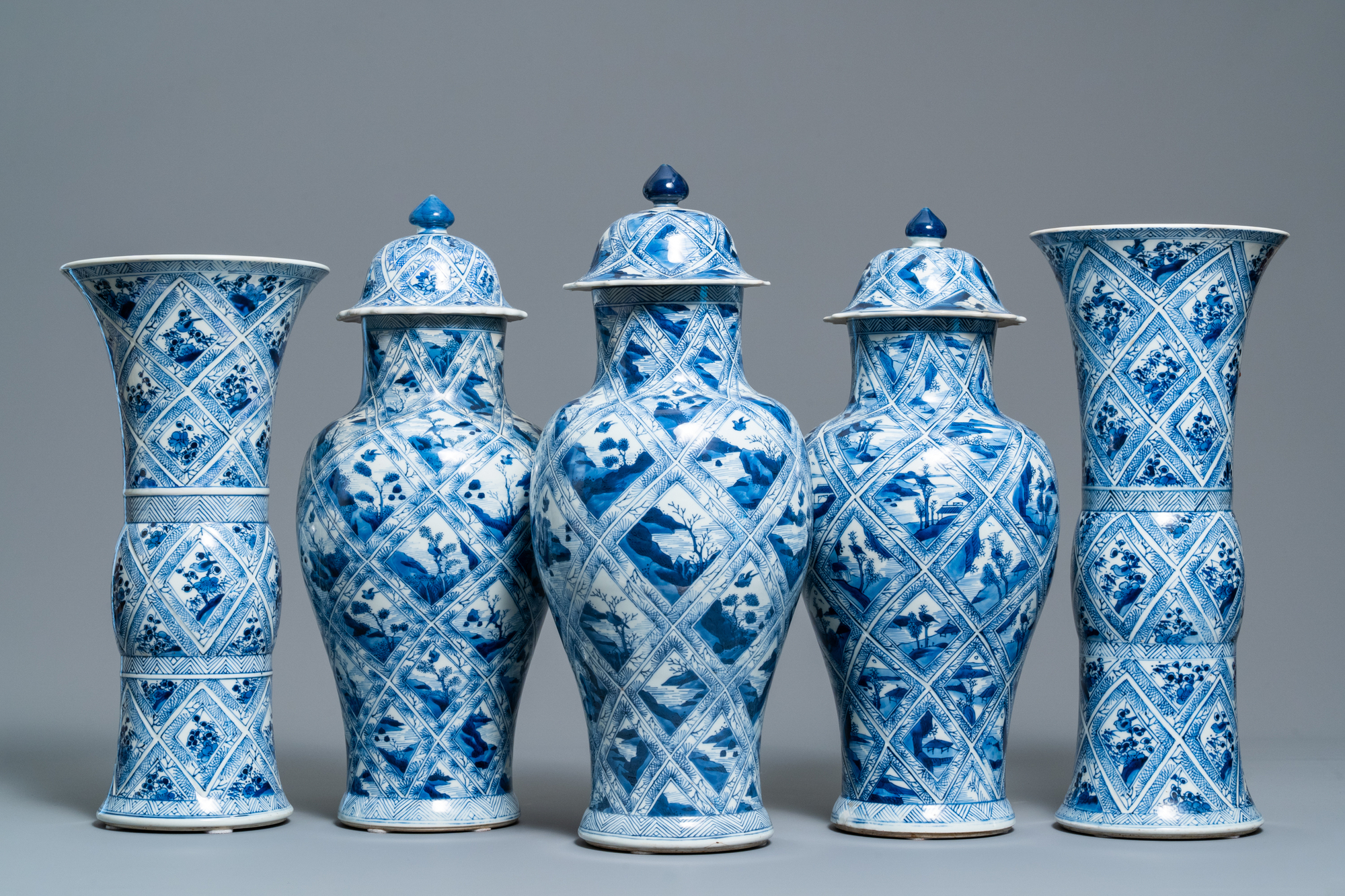 A large Chinese blue and white five-piece garniture with floral and landscape panels, Kangxi