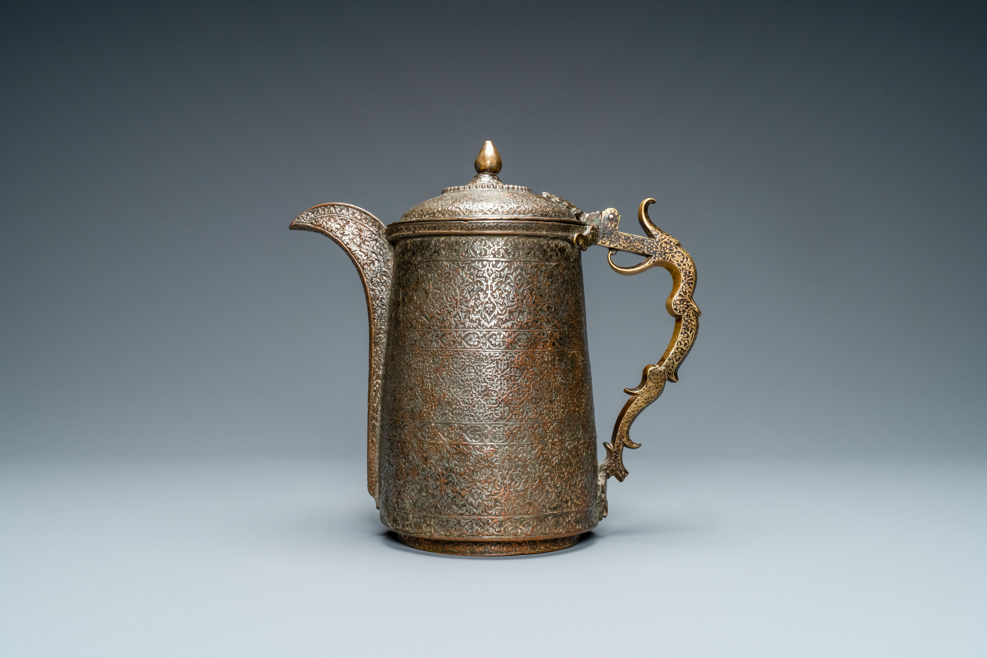 A Safavid parcel-gilt and tinned copper mug and cover, Persia, 17/18th C.