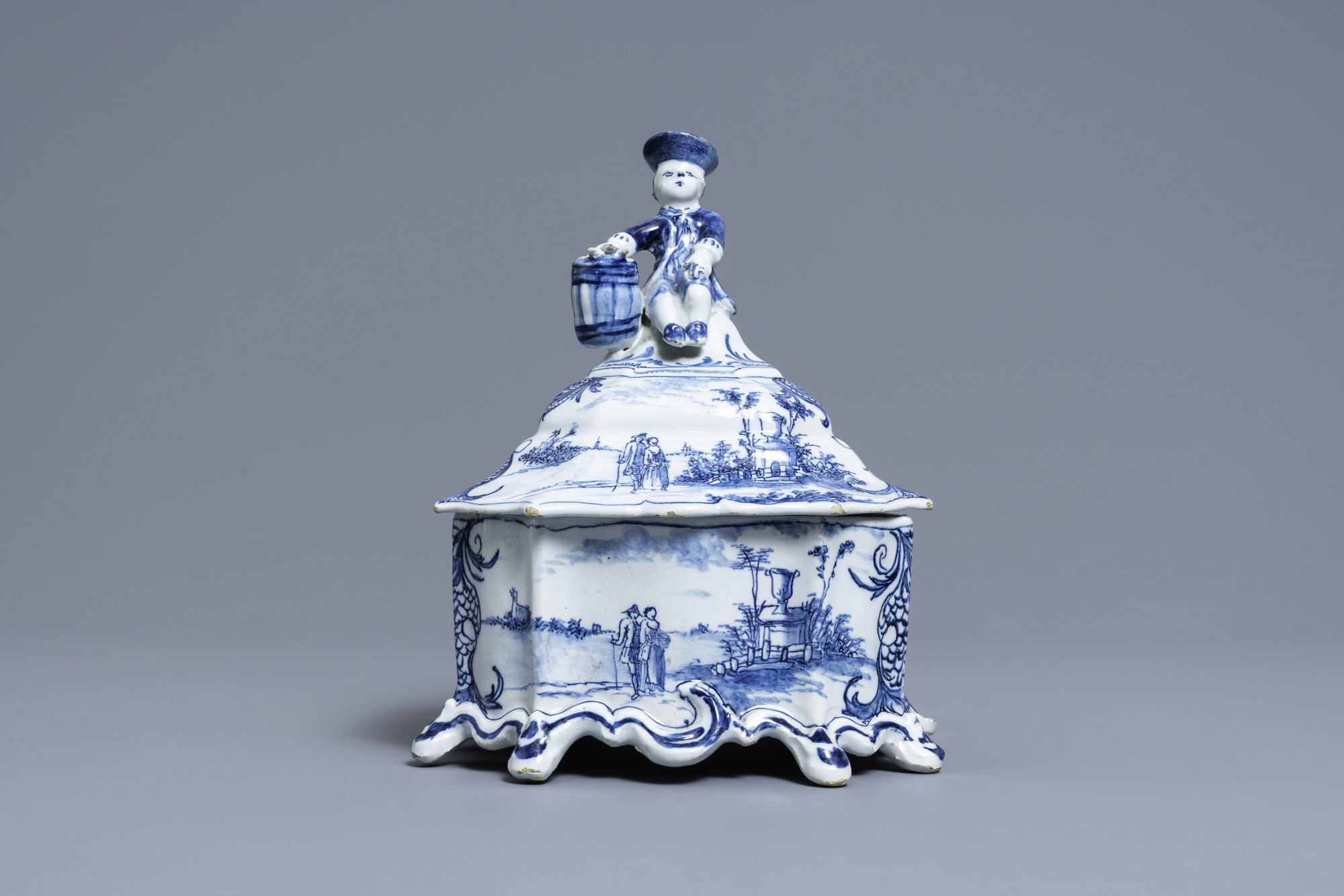 A Dutch Delft blue and white tobacco box and cover with a boy near a barrel, 18th C.