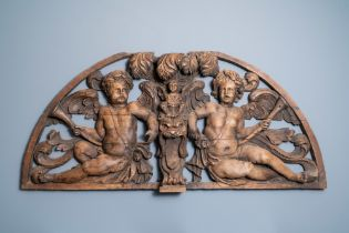 A reticulated carved oak fronton with two winged cherubs holding a horn, France, 17th C.