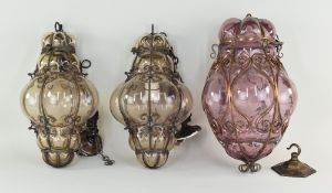 THREE VENETIAN GLASS & METAL FRAMED HALL LANTERNS, comprising a pair in smoky glass, 30cms high, and