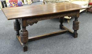 ELIZABETHAN-STYLE OAK REFECTORY TABLE, boarded top above channel carved frieze with scrolled