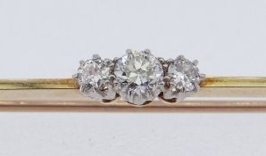 THREE-STONE DIAMOND BAR BROOCH in yellow metal setting, diamond weight 0.2ct overall (visual