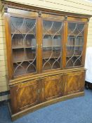 MAHOGANY CONCAVE REPRODUCTION BOOKCASE with dentil shaped cornice, over three upper glazed doors
