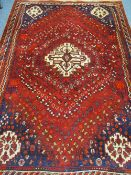 AN EASTERN STYLE RED GROUND WOOLLEN CARPET with central light colour block on a red ground with blue
