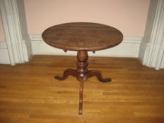 19TH CENTURY CIRCULAR OAK TRIPOD TABLE having centre turned pedestal on pad supports, 85cms