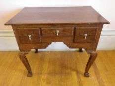 CIRCA 1820 OAK LOWBOY having two plank rectangular top over three drawers and shaped apron with