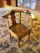 ANTIQUE ELM CORNER FARMHOUSE ELBOW CHAIR having a curved back with twin shaped splats and turned