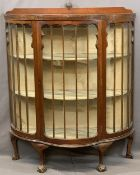 EDWARDIAN MAHOGANY SERPENTINE FRONT CHINA DISPLAY CABINET with single central door, fabric covered