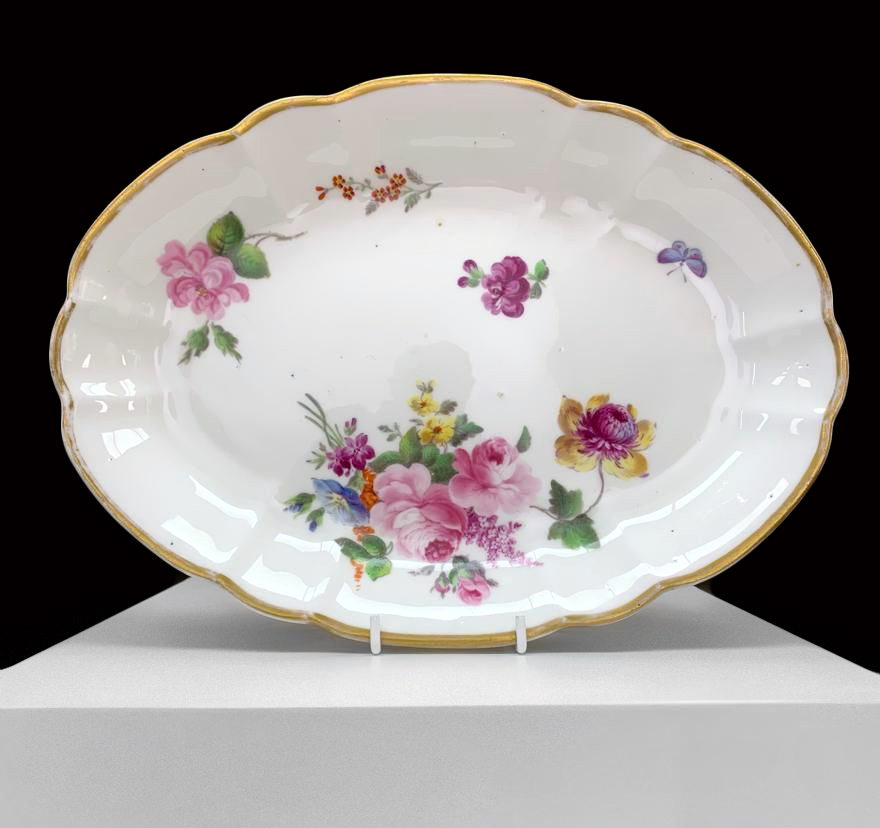 A NANTGARW PORCELAIN OVAL DISH of lobed form and decorated with a large off-centre spray of flowers,