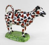 A SWANSEA CAMBRIAN PEARLWARE COW CREAMER typically modelled with tail loop-handle and standing on