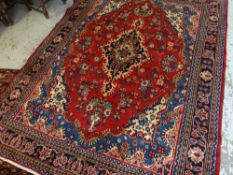 TABRIZ RUG, indigo and beige medallion on a deep red field, royal blue, ivory and salmon