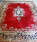 KIRMAN CARPET, indigo and ivory rectangular medallion with pendants on a plain cherry red field with