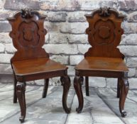 PAIR OF VICTORIAN WALNUT HALL CHAIRS, carved shield backs, solid seats and scrolled legs, 94cms high