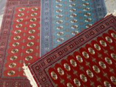 THREE MODERN AFGHAN-STYLE RUGS, identical Bakhara designs in pink, red and teal fields, 170 x 120cms
