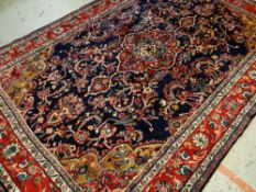 TABRIZ-STYLE RUG, red medallion on an indigo field with caramel and pink spandrels, red palmette