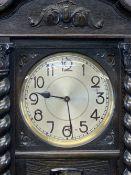 CIRCA 1930 CARVED OAK LONGCASE CLOCK with barley twist Corinthian cap front detail, chime strike