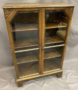 VINTAGE OAK TWO DOOR GLAZED BOOKCASE having bevelled edging to the glass and interior adjustable