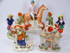 STAFFORDSHIRE COW SPILL HOLDERS, other figural groups and a cottage including a Jockey on horseback,