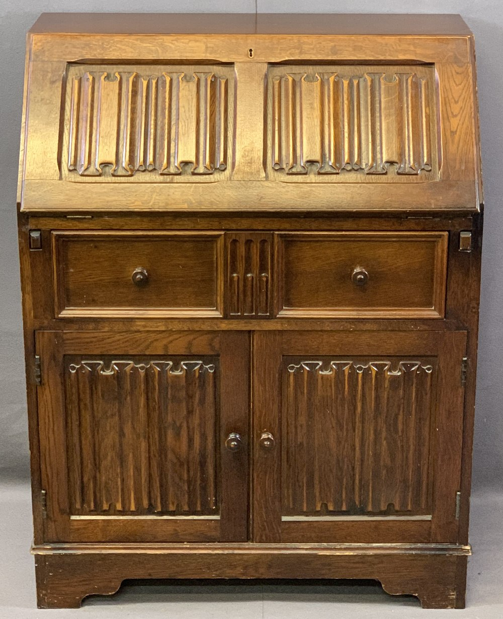PRIORY STYLE OAK LINENFOLD CARVED FALL-FRONT BUREAU, the fall interior with a fitted arrangement