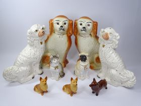 STAFFORDSHIRE & OTHER POTTERY DOG FIGURINES and a biscuit porcelain cat, 34cms H the largest pair